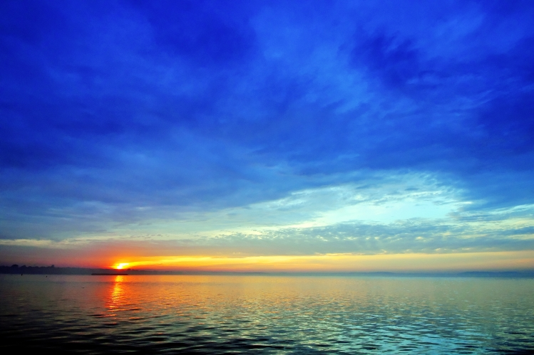 A sunset over a lake with a deep blue sky.