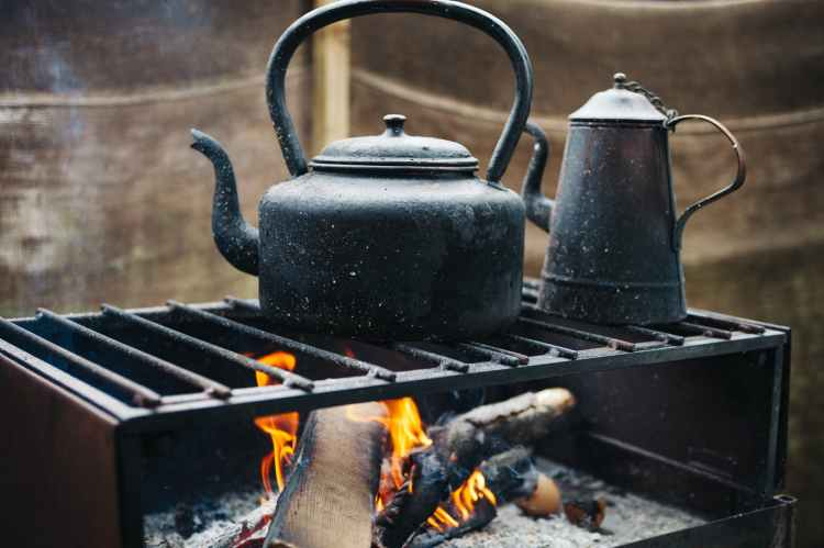 A rustic photo of an old-style tea kettle and coffee urn over an open flame outdoors.
