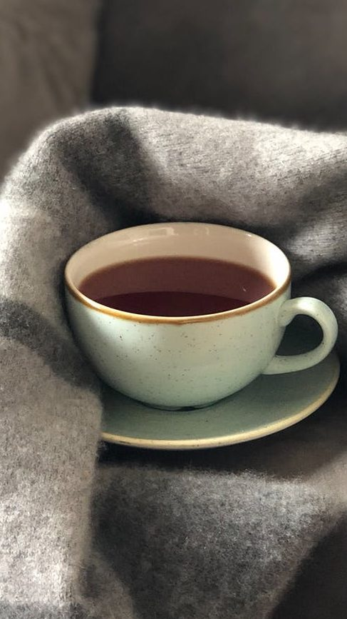 A cup of coffee snuggled by a warm gray fuzzy blanket.