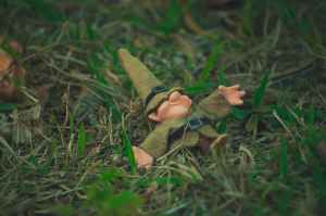 A funny photo of a small gnome made of cloth laying in the grass on his back.