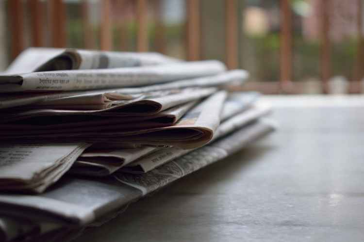 A close-up photo of multiple newspapers loosely stacked on a wooden table.