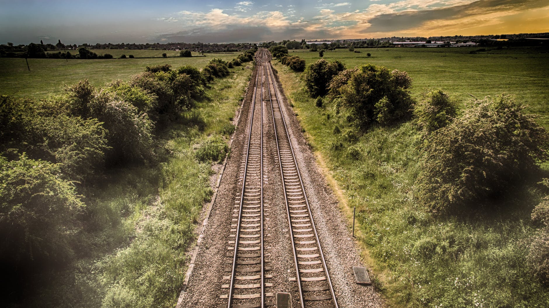 A photo of some railroad tracks that lead off into the distance with a green landscape of fields and trees.