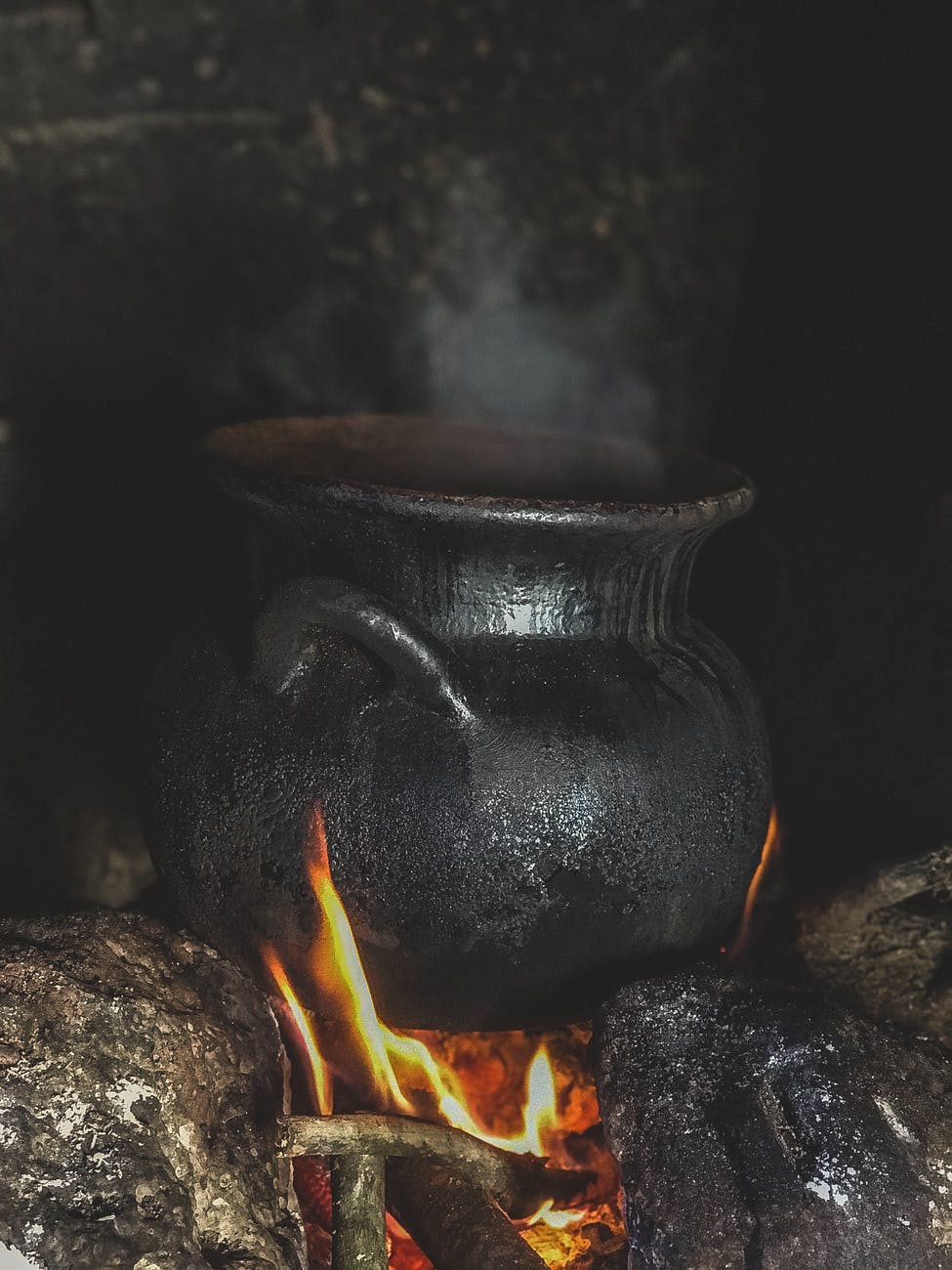 A photo of a cauldron over an open flame.