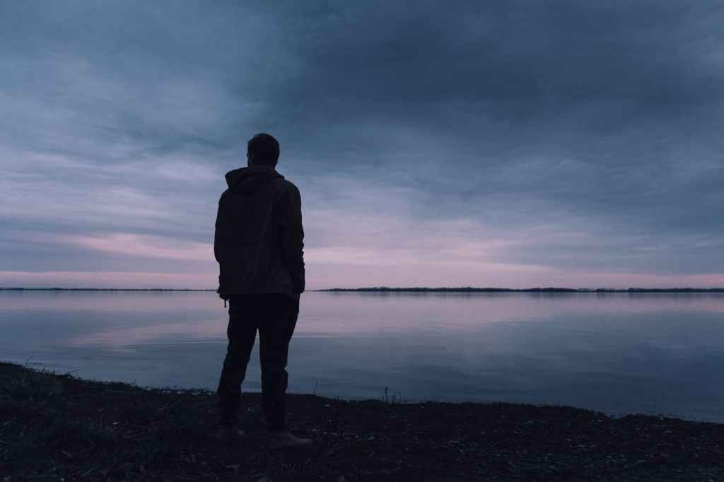 A man standing at the edge of a lake with dark skies.