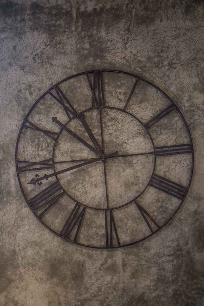 A photo of a big clock with roman numerals affixed to a stone background.