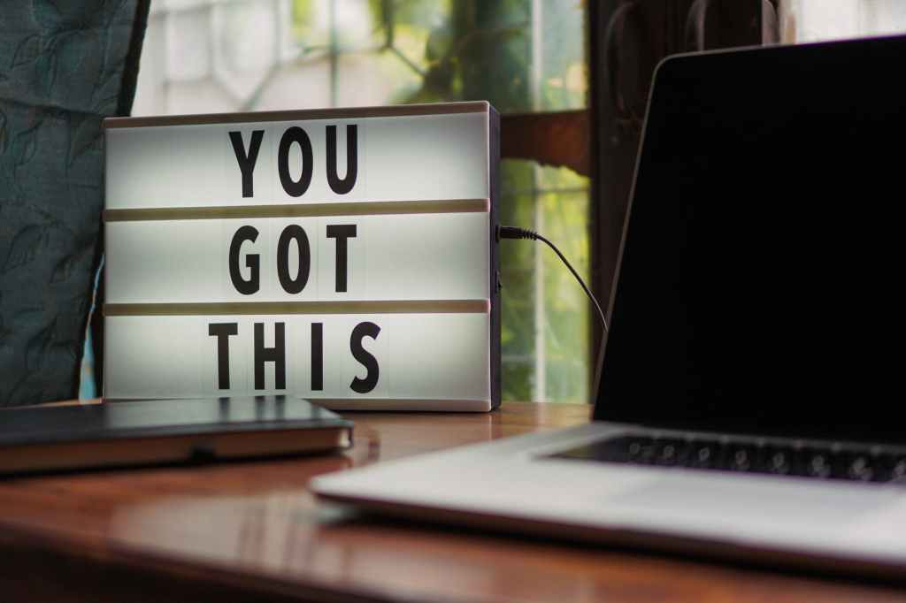 A photo showing the words You Got This next to a laptop on a desk.