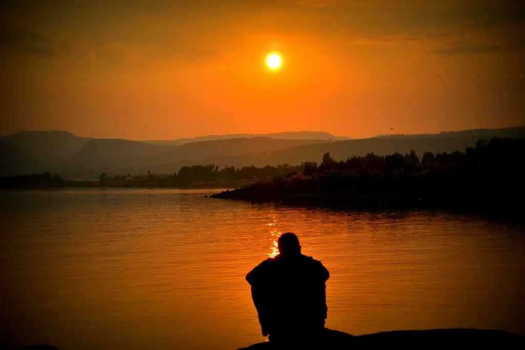 A photo of a man sitting at the edge of a lake at sunset.